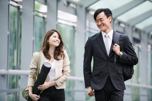 オフィス街を歩くビジネスマンとビジネスウーマンの写真素材 [FYI01802116]