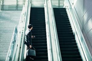 エスカレーターに乗るビジネスマンの写真素材 [FYI01802134]