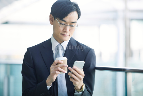 スマートフォンをもつビジネスマンの写真素材 [FYI01802135]