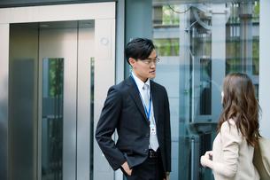 オフィスビルの前で話すビジネスマンとビジネスウーマンの写真素材 [FYI01802136]
