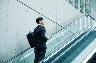タブレットPCを持ちエスカレーターに乗るビジネスマンの写真素材 [FYI01802142]