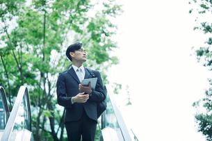 タブレットPCを持ちエスカレーターに乗るビジネスマンの写真素材 [FYI01802152]