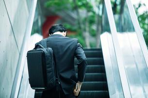 タブレットPCを持ちエスカレーターに乗るビジネスマンの写真素材 [FYI01802158]