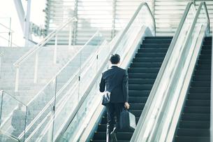 エスカレーターに乗るビジネスマンの写真素材 [FYI01802161]