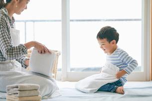 洗濯物をたたむ男の子と女性の写真素材 [FYI01802168]