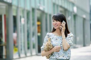 スマートフォンを持ち街を歩く女性の写真素材 [FYI01802179]