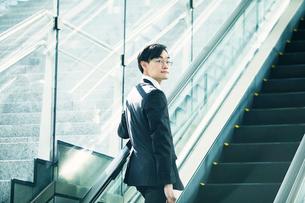 エスカレーターに乗るビジネスマンの写真素材 [FYI01802180]