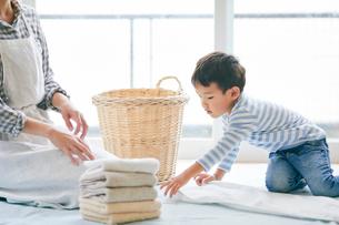 洗濯物をたたむ男の子と女性の写真素材 [FYI01802187]