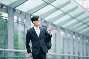 スマートフォンを持ちオフィス街を歩くビジネスマンの写真素材 [FYI01802207]