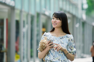 スマートフォンを持ち街を歩く女性の写真素材 [FYI01802232]