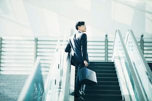 エスカレーターに乗るビジネスマンの写真素材 [FYI01802233]