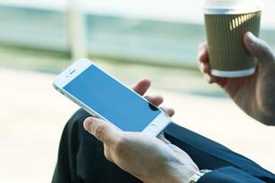 スマートフォンを持つビジネスマンの手の写真素材 [FYI01802264]