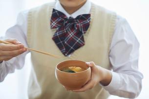 お椀を持ち味噌汁を食べる女子学生の写真素材 [FYI01802285]