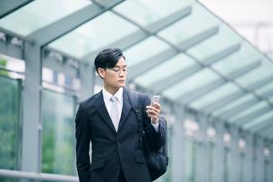 スマートフォンを持ちオフィス街を歩くビジネスマンの写真素材 [FYI01802293]
