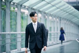 スマートフォンを持ちオフィス街を歩くビジネスマンの写真素材 [FYI01802314]