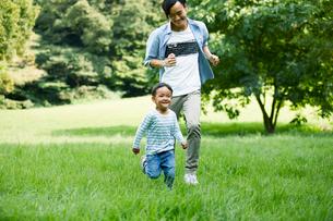 緑の中で遊ぶ家族の写真素材 [FYI01802322]