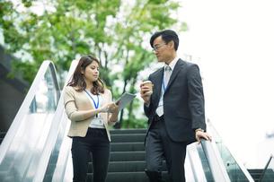 会話しながらエスカレーターに乗るビジネスマンとビジネスウーマンの写真素材 [FYI01802328]