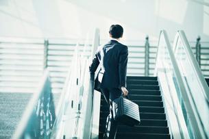 エスカレーターに乗るビジネスマンの写真素材 [FYI01802335]
