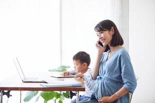 仕事をする女性とタブレット端末を見る男の子の写真素材 [FYI01802349]