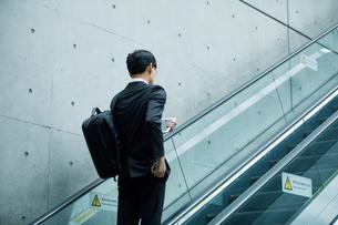 タブレットPCを持ちエスカレーターに乗るビジネスマンの写真素材 [FYI01802354]