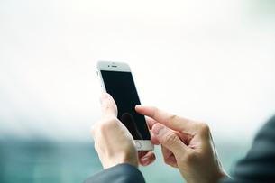 スマートフォンをもつビジネスマンの写真素材 [FYI01802363]