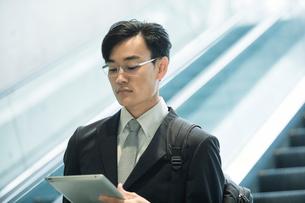 タブレットPCを持ちエスカレーターに乗るビジネスマンの写真素材 [FYI01802364]