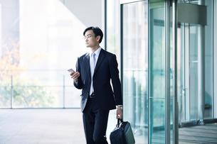 スマートフォンをもつビジネスマンの写真素材 [FYI01802373]