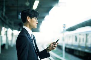スマートフォンをもつビジネスマンの写真素材 [FYI01802377]