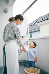 洗濯物を干す女性と男の子の写真素材 [FYI01802387]