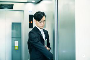 タブレットPCを持ちエレベーターに乗るビジネスマンの写真素材 [FYI01802405]