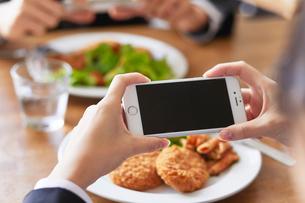 食事の写真を撮る女性とスマートフォンの写真素材 [FYI01802413]