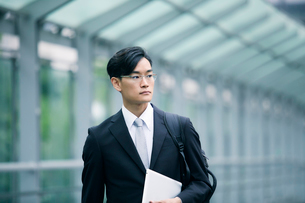 タブレットPCを持ちオフィス街を歩くビジネスマンの写真素材 [FYI01802416]