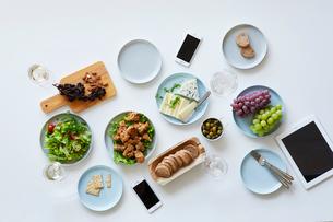 テーブルに載せた料理とスマートフォンとタブレットPCの写真素材 [FYI01802432]