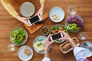 料理の写真を撮る男女の写真素材 [FYI01802439]