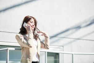 ビルの前に立ちスマートフォンを持つ女性の写真素材 [FYI01802444]