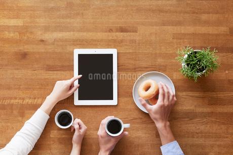 タブレットPCを見る女性と男性の手の写真素材 [FYI01802445]