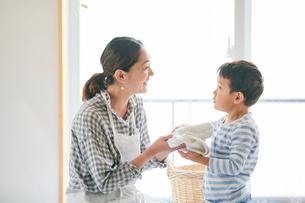 洗濯物をたたむ男の子と女性の写真素材 [FYI01802475]
