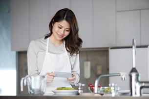 キッチンに立ち写真を撮る女性の写真素材 [FYI01802481]
