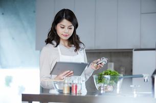 タブレットPCを持ち料理を作る女性の写真素材 [FYI01802491]