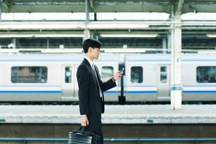 スマートフォンをもつビジネスマンの写真素材 [FYI01802502]