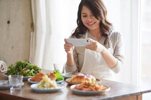料理の写真を撮る女性の写真素材 [FYI01802511]