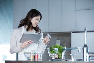 タブレットPCを持ち料理を作る女性の写真素材 [FYI01802572]