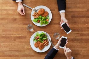 食事をする女性と男性とスマートフォンの写真素材 [FYI01802579]