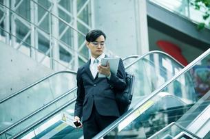 タブレットPCを持ちエスカレーターに乗るビジネスマンの写真素材 [FYI01802582]