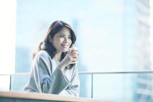 カフェでコーヒーカップとタブレットPCを持つ女性の写真素材 [FYI01802585]