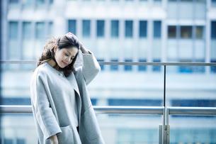 オフィス街でスマートフォンを持つ女性の写真素材 [FYI01802589]