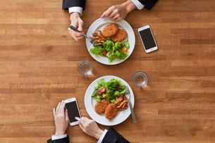 食事をする女性と男性とスマートフォンの写真素材 [FYI01802629]