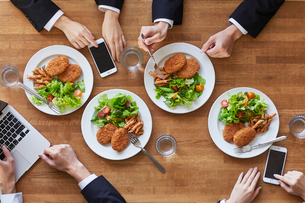 食事をする女性と男性とスマートフォンの写真素材 [FYI01802630]