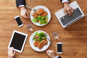 食事をする女性と男性とスマートフォンの写真素材 [FYI01802633]