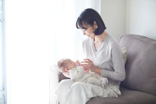 赤ちゃんを抱っこする母親とミルクを飲む赤ちゃんの写真素材 [FYI01802634]